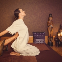Professional thai masseuse is stretching female body. She is raising leg to her back. Young woman is sitting on floor. Her eyes are closed with pleasure